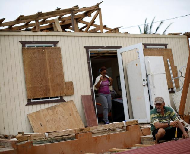 Julio Morales looks for valuables outside his damaged house after the area was hit by Hurricane...