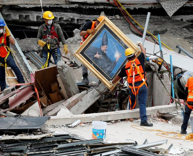 Mexican and international rescue teams remove a painting as they search for survivors in a collapsed building on Saturday. Photo: Reuters