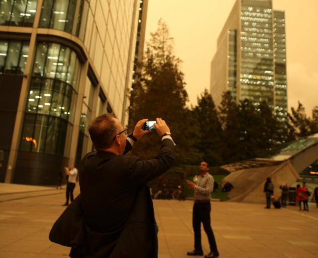 A man photographs the sky turning reddish yellow over buildings in Canary Wharf. Photo: Reuters
