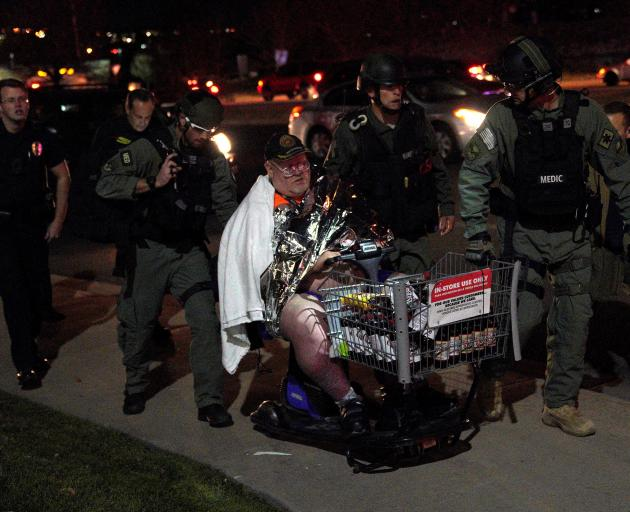 Shopper Patrick Carnes is evacuated in a cart by SWAT medics from the scene of the Walmart shooting. Photo: Reuters
