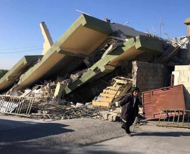 A man walks past a damaged building following an quake in Darbandikhan in northern Iraq. Photo:...