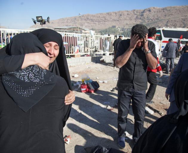 Women comfort each other in Sarpol-e Zahab county in Kermanshah. Photo: Reuters