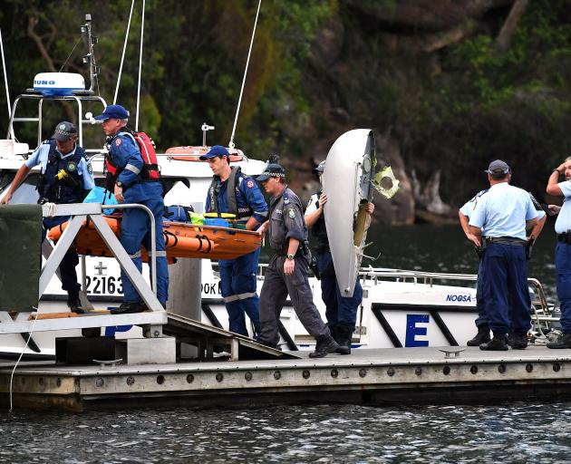 Emergency staff carry the body of a passenger recovered from the seaplane. Photo: Reuters