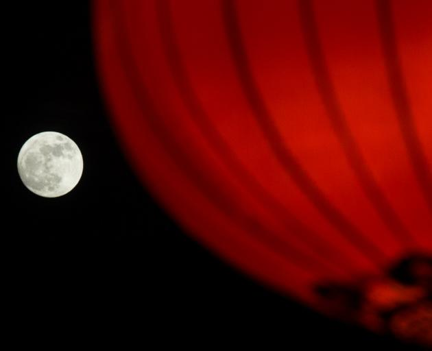 The supermoon seen rising behind a red lantern in Beijing on January 1. Photo via Reuters