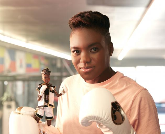 British boxer and Olympic gold medallist Nicola Adams holds a Barbie doll made in her likeness to...