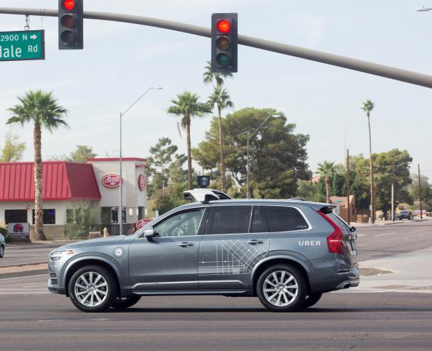 A self-driving Volvo vehicle, purchased by Uber, moves through an intersection in Scottsdale,...