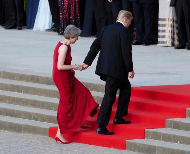 Donald Trump leads Theresa May by the hand as they climb the steps to the entrance of Blenheim...