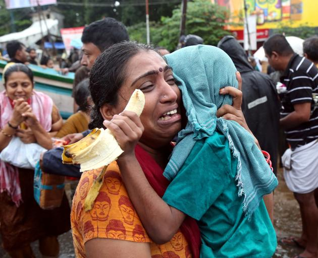 A distraught woman  holds her son after being evacuated from a flooded area in Aluva in the...