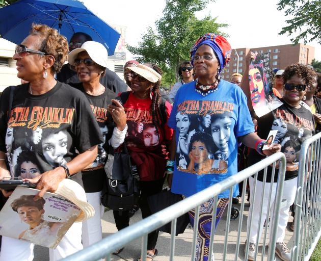 Fans wait outside the Charles H. Wright African American Museum in Detroit to see the body of...