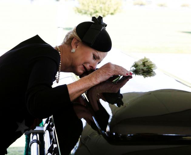 Cindy McCain lays her head on the casket of husband John McCain at the service on Sunday. Photo: ...