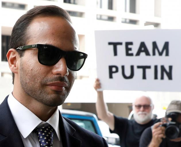 A protester holds a banner as former Trump campaign aide George Papadopoulos arrives for his...