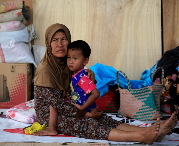 A woman and son rest outside their house for safety reasons in quake-hit Biromaru village on the...