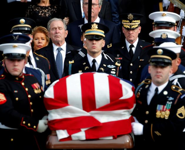 Ex-President George W. Bush follows a military honour guard as they carry the casket of his...