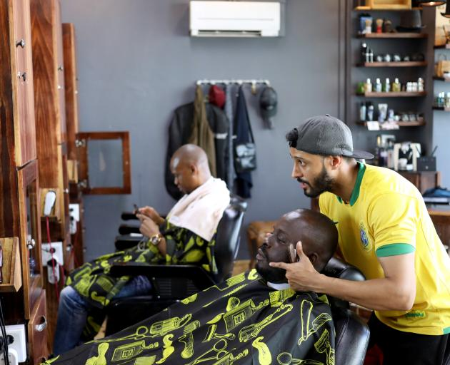 A worker grooms a client at the Bespoken Man, a full-service gentleman's barber shop in...