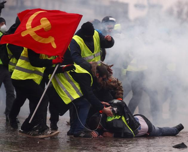 Protesters wearing yellow vests help a person injured by a water cannon during a demonstration by...