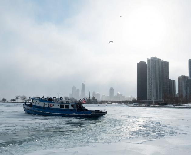 Icebreaker tugboat the James J. Versluis ploughs through a frozen Lake Michigan. Photo: Reuters