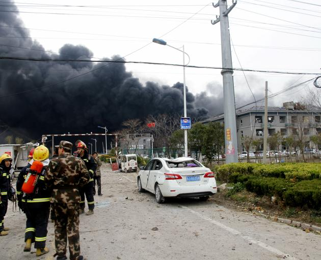 Rescue workers are seen near smoke following an explosion at a chemical industrial park in...