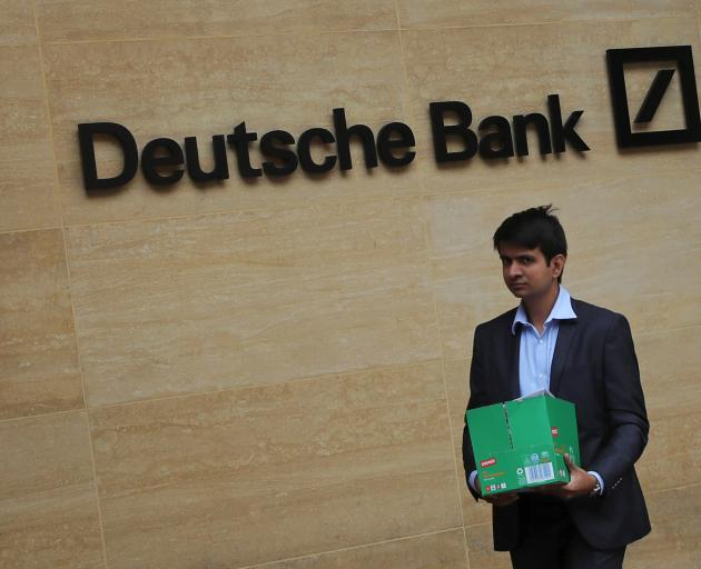 A worker leaves Deutsche Bank's London office. Hundreds of jobs were set to go there. Photo:...