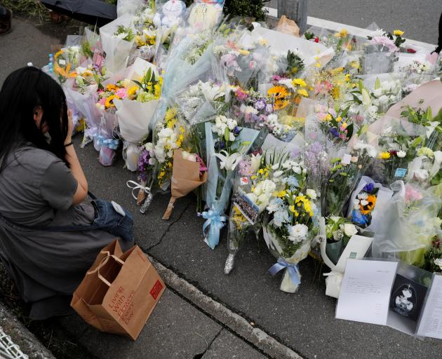 A woman prays in front flowers left for the victims. Photo: Reuters
