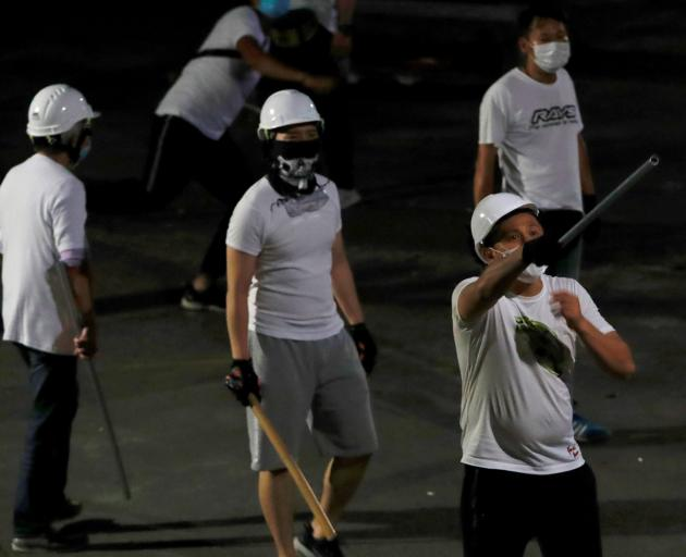 Men in white T-shirts, some armed with clubs, flooded into the rural Yuen Long station and...