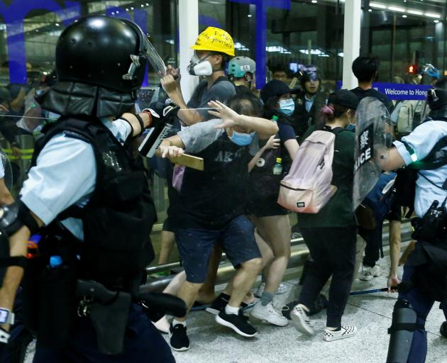 A police officer sprays pepper spray at anti-government protesters. Photo: Reuters