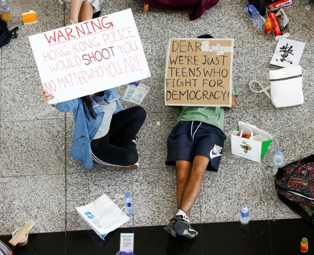 Anti-government demonstrators sit in a designated area of the arrival hall of the airport. Photo:...