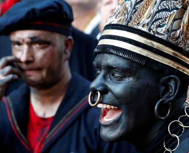"""""""The Savage"""", a white performer in a blackface disguise, takes part in the festival Ducasse d'Ath..."""