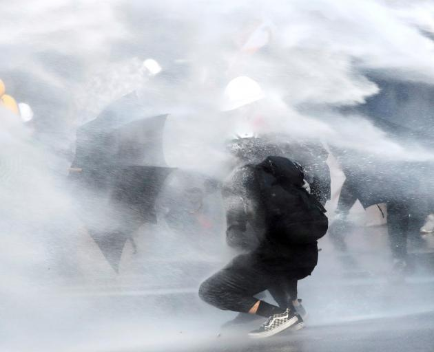 Anti-government protesters are sprayed with water cannon during a demonstration near Central...