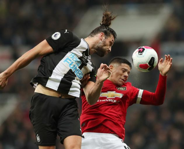 Newcastle United's Andrew Carroll (left) and Manchester United's Marcos Rojo compete for the ball...