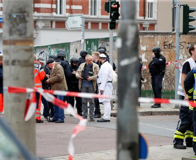 A police officer speaks with a Jewish man as he is being escorted from from the site of the...