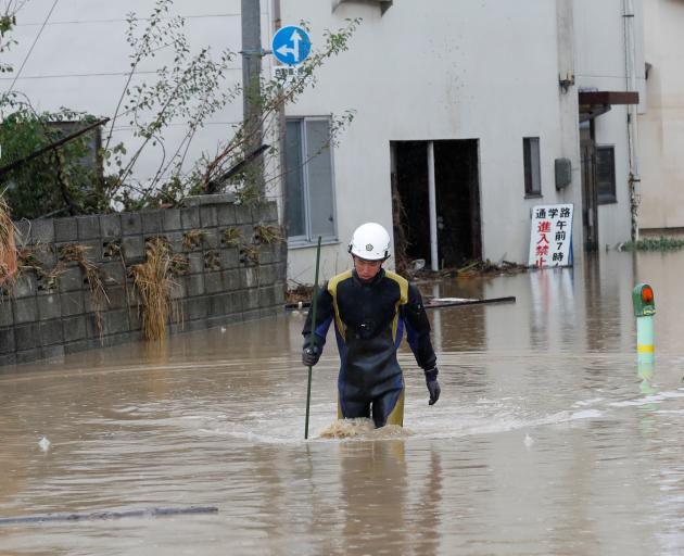 A rescue worker wades in water in the aftermath of Typhoon Hagibis, which caused severe floods,...