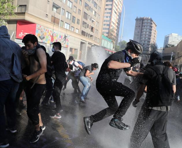Demonstrators try to avoid water sprayed during a protestin Santiago on Monday. {Photo: Reuters)