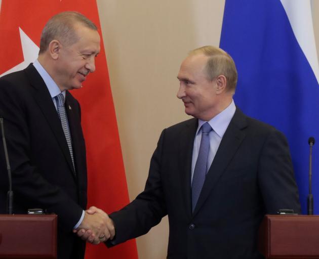 Turkish President Recep Tayyip Erdogan (left) shakes hands with Russian leader Vladimir Putin....
