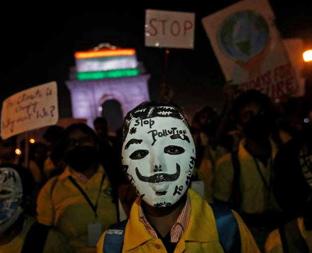 A boy wears a mask attends a protest demanding government to take immediate steps to control air...