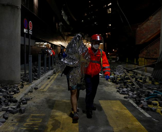 A protester is escorted by medical staff out of the Hong Kong Polytechnic University on Wednesday...