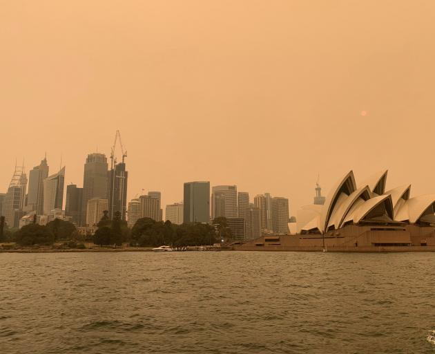 The haze from bushfires obscures the sun setting above the Sydney Opera House in Sydney. Photo:...