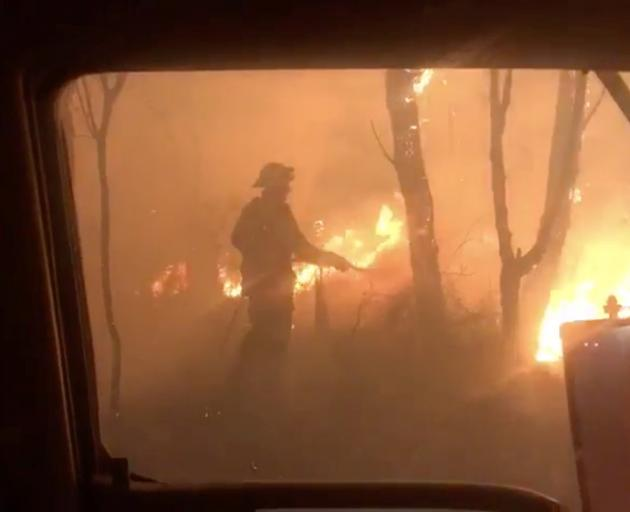 A firefighter attempts to control fire in Newnes Plateau in New South Wales at the weekend. Photo...