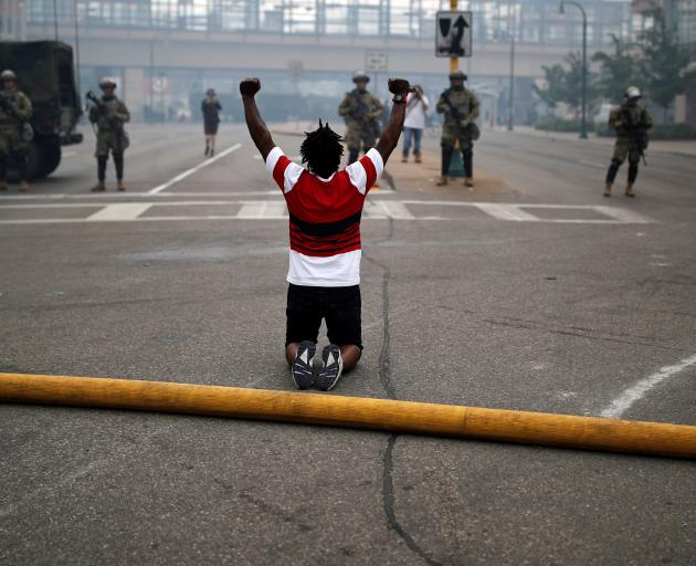 A man gestures as he confronts National Guard members guarding the area in the aftermath of a...