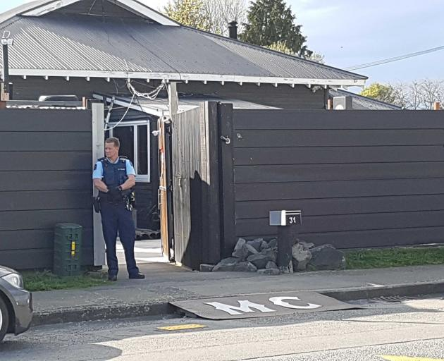 Armed police outside a Vickerys Rd property linked to the Head Hunters. Photo: Geoff Sloan
