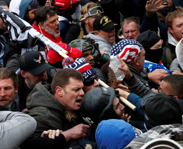 Pro-Trump protesters clash with Capitol police at a rally to contest the certification of the...