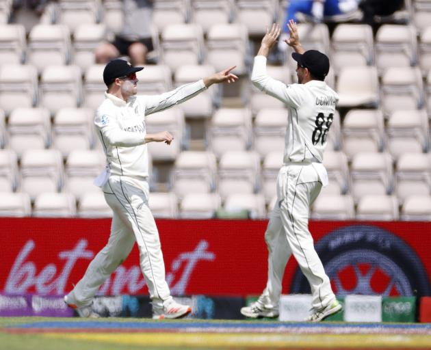 New Zealand's Henry Nicholls celebrates with Devon Conway after taking a catch to dismiss India's...