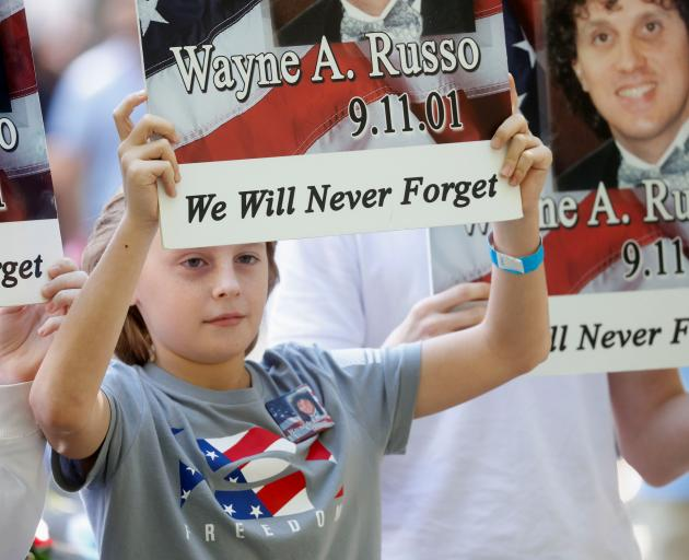 Signs remembering those killed in 9/11 were held at the ceremony in New York on Saturday. Photo:...