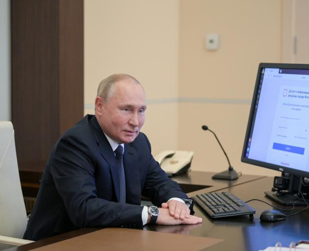 Russian President Vladimir Putin sits in front of a computer while taking part in remote...