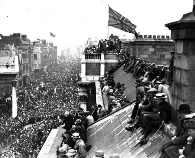 People sit and stand atop Trinity College's West Front building, which is flying the Union Jack,...