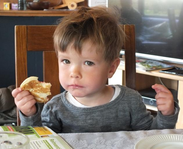 Ben Rutherford (2)  takes a break from gardening to sample a pikelet with Grandma's homemade...