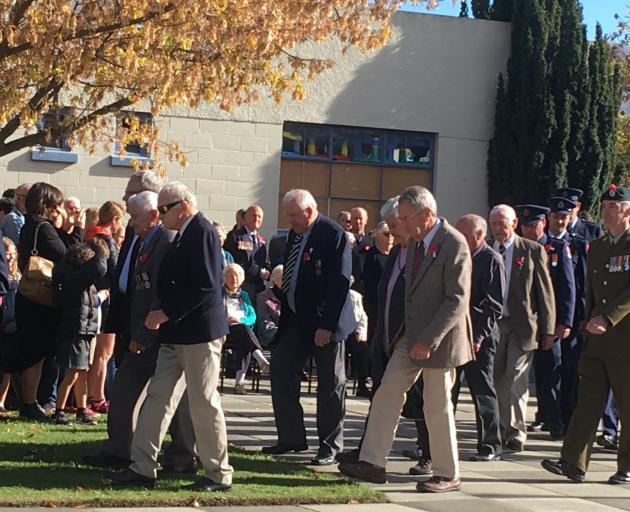 Anzac Day representatives form a procession during commemorations at the Cromwell cenotaph during...