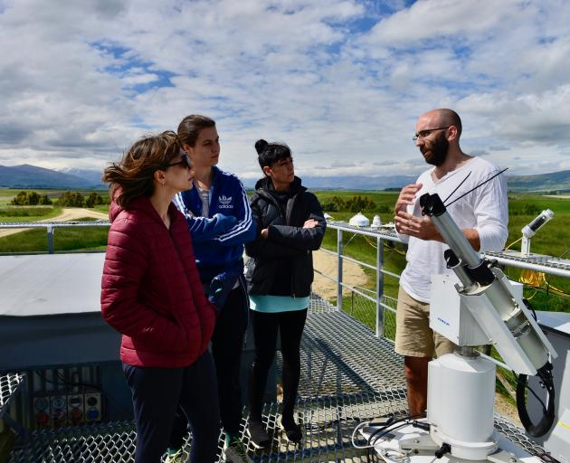 Lauder Niwa scientist Dr Alex Geddes talks to Lungsong dancers among UV instruments on the roof...