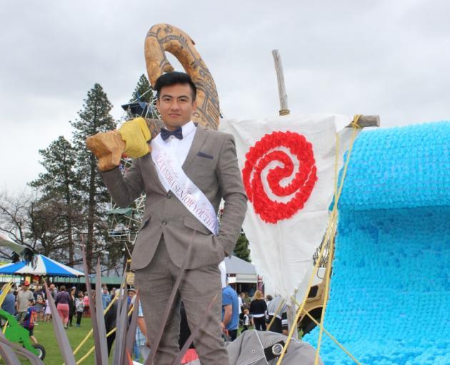 Blossom Festival prince Jeff Afan holds a Maui fish hook on a Moana-themed float. PHOTO: JONO...