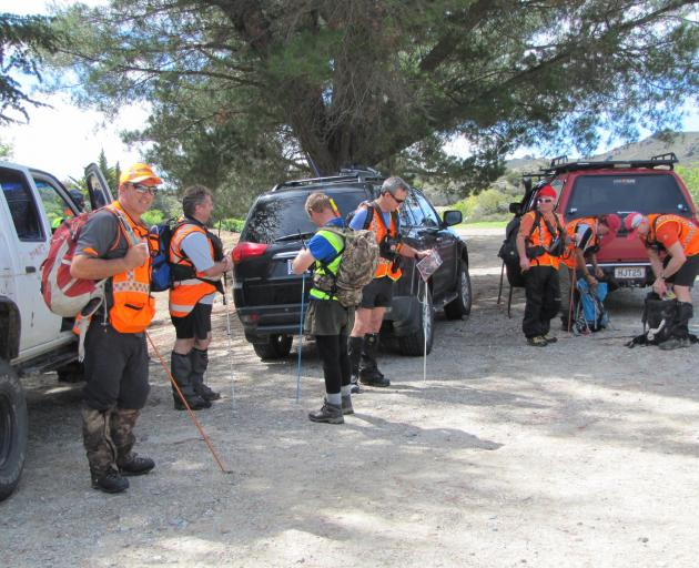Land Search and Rescue volunteers prepare to search for a missing man in the Alexandra railroad...