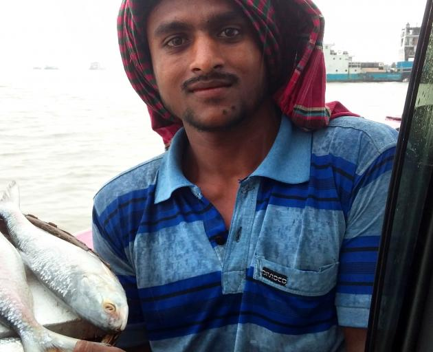 A fish seller plies his trade on the Padma RIver Ferry.